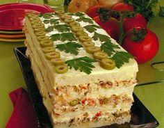 Torta gelada com pão integral e camadas de patê de atum ou frango e azeitonas por cima.