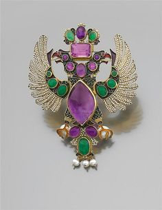 """A Multi-gem pearl, gold brooch by Roquemaurel Galitzine. The Great Countess hat pin """"eagle Romanov"""" It is a two-headed eagle with outstretched wings and a crown. The set is embellished with emeralds, amethysts, pearls and seed pearls. Frame 18K yellow gold enamel. Signed work ROQUEMAUREL GALITZINE Gross Weight: 49.4 gr. Dimensions: 9.5 x 7.5 cm"""