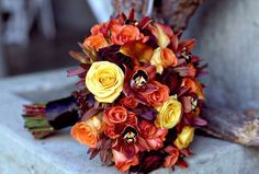 Bouquet composed of Conga, Tropical Amazon and Black Bacara Roses with Mango Calla Lilies, Leucodendron 'Safari Sunset', Brown Cymbidium Orchids and Orange Spray Roses. Finished with Espresso Satin Ribbon and Brown crystal trim.