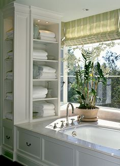 Storage by built in tub.....wide, beautiful tub surround....