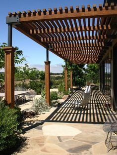 modern house exterior wooden pergola natural stone flooring patio furniture