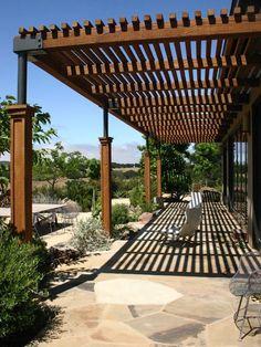 modern house exterior wooden pergola natural stone flooring patio furniture