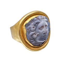 Ancient Roman Medusa Cameo Ring. Ancient Roman agate cameo ring in hammered gold, the cameo sculpted in high relief with the facing head of Medusa, her face framed by serpentine locks with two short wings above her forehead, the agate circa 2nd century A.D. and mounted in a modern gold ring. Italy, 2nd century AD