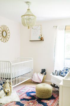 Neutral nursery with pretty chandelier featuring Caitlin Wilson Navy Kismet Rug