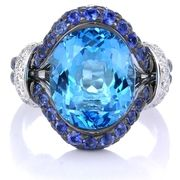 Diamond Blue Sapphire & Blue Topaz 18k White Gold and Black Rhodium Ring-  This handcrafted 18k white gold and Black Rhodium ring, features one honeycomb oval cut blue topaz, of exquisite color, weighing 6.20 carats, with round cut blue sapphires, of exquisite color, weighing 1.45 carats total and round brilliant cut diamonds, of F color, VS2 clarity, and excellent cut and brilliance, weighing .30 carat total.    Retail Price:$14,175 Special Offer Price:$6,325