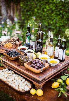 An olive oil tasting station with olives, bread, and dried fruit.