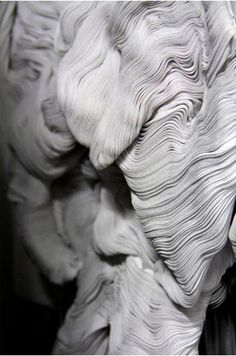 Sculptural fabric manipulation - close up dress detail with micro pleat textures arranged in the shape of a face; art with fabric // Yiqing Yin