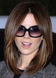 Actress Kate Beckinsale looks smoldering hot with her symmetrical, rounded bob and a huge pair of sunnies. Kate's middle parting allows her hair to skim across her forehead, accentuating her eyes and mouth. By keeping the upper corners of her forehead concealed, Kate draws attention away from the top half of her face, making her overall profile seem less long and narrow.