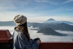 Buy Young traveler looking at beautiful view of Mount Bromo volcano by kitzstocker on PhotoDune. Young traveler looking at beautiful view of Mount Bromo volcano (Gunung Bromo) during sunrise from viewpoint in East . Volcano, Trekking, Mists, Tourism, Sunrise, Clouds, Stock Photos, Adventure, Vacation
