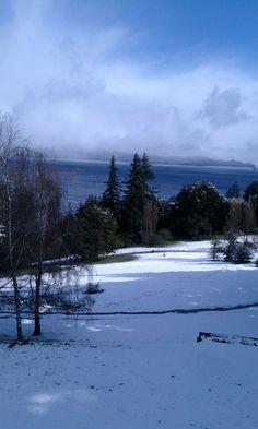 Pasos en la nieve y el incomparable vista del lago desde el parque del hotel Tunquelén en Bariloche. Argentina. Octubre 2015