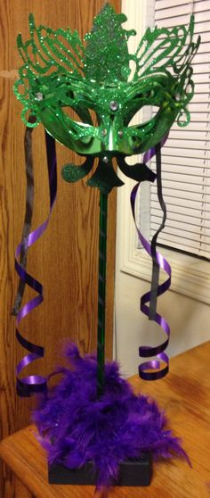 Mardi Gras centerpiece for work party 2014. Dad made the stand, Fleur de lys topper is from Michaels. Mom and I designed each theme per piece.