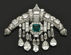 "Emerald and Diamond Sarpech Brooch   Worn by Queen Elizabeth at Royal Ascot, June 13, 2013.  Labeled as a sarpech, or ""turban ornament that was worn by significant Hindu and Muslim princes"". Made in 1920, it is an Art Deco design of Indian inspiration featuring a curved central shape set with diamonds in platinum and white gold. Below, an emerald set with a diamond surround sits between diamond tassels with diamond pendants. It sold at Christie's Paris in Nov 2011 for €49,000, ($65,643)."