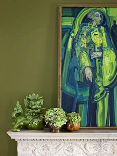 """Olive + Lime + Teal - """"typical combinations are either muddy, earthy tones or vibrant, bold hues when working with green. This vignette combines the two. The olive-green walls have brown undertones and are paired with a painting featuring shades of lime and teal. The olive-green wall serves as a neutral backdrop to the painting's brighter hues. """""""
