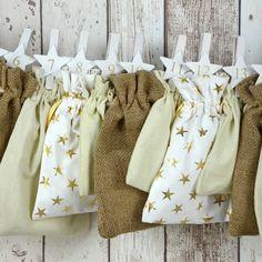 """All-Inclusive Adventskalender """"Sternengold"""". Stimmungsvoller Mix von Geschenksäckchen in creme, mit goldenen Sternen und aus Jute."""