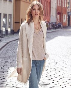 Aneta knitted coat - A lightweight, fluffy alpaca coat with a wide edge-to-edge collar in a ribbed cotton. The contrasting weight of the ribbed cotton keeps the shape and structure and allows the warm and cosy alpaca to wrap around you. With two jetted pockets and fringed hem.