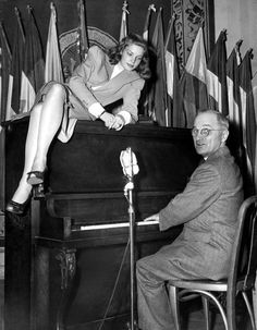 Lauren Bacall sits on a piano while Vice President Harry Truman plays (1945)