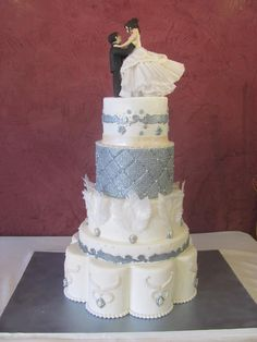 Devil's Food Cake with Chocolate Rasberry Buttercream Filling, Dark Chocolate Ganache covered in Fondant. Rice Paper Feathers, Dragees, Bride And Groom Cake Toppers are made of Fondant, Brides Dress is Fondant, Rice Paper and Sugar Beads.