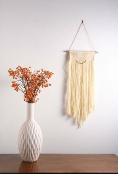 """Off White / Cream Modern Macrame Fiber Art Wall Hanging Tapestry on Wood Bar w/ Brass Accent.   The """"Vintage Modern"""" Macrame Wall Hanging Collection is inspired by my love for mid century modern and contemporary design. There is nothing wrong with mixing the old with the new! The pieces in this collection are so versatile that they would be a great accent to any space or decor style.  Size: Large Materials: 100% wool fibers + brass + wood      Dimensions: 12""""w x 27""""h Total height with"""