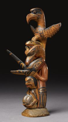 """KWAKIUTL POLYCHROME WOOD MODEL TOTEM POLE    carved with a human figure in a crouching posture, surmounted in turn by abear with a killer whale in his jaws, a fish, and a thunderbird, with outstretched wings, painted overall in red, yellow, black and blue, with typical stylized crest designs; signed on the back """"Charl Jamson, Yakuglas"""" (Charlie James, b. 1870, Port Townsend, WA).  height 14 1/4 in."""