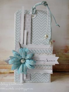 handmade tag ... pastel aqua with gray and white ... dimensional blue daisy with a huge pearl in the center ... chevron print papers in the palest gray and aqua ... stiched edges ... columns of paper ... delightful tag!!