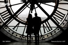 Britain's Prince William, Duke of Cambridge, and his wife Britain's Kate, Duchess of Cambridge, look across the River Seine at a view of Paris through the clock face at the Musee d'Orsay - the former...