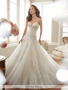 "WEDDING DRESSES by Sophia Tolli, these bridal gowns provide both classic and couture designs including strapless ball gowns, A-line dresses, halters and slim skirts. Wedding dresses with Sophia's signature draping and corset backs provide an impeccable fit. Sophia adds, ""My collection has two distinct feelings: soft romanticism and traditional bridal drama. My signature style will always be gowns with an exceptional fit and cut."""