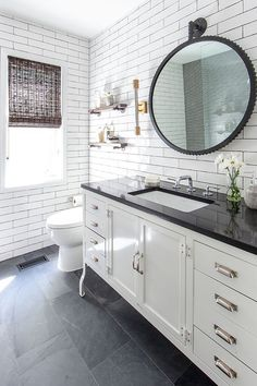 Slate on the floor with a white furniture style vanity with a black quartz count.- Slate on the floor with a white furniture style vanity with a black quartz countertop + round black mirror + white subway tile covering the whole bathroom Slate Bathroom, White Subway Tile Bathroom, Bathroom Floor Tiles, Black Bathroom Floor, Floor Mirror, Black And White Master Bathroom, Black Slate Floor, Bathroom Ideas, Black White Bathrooms
