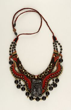 Cooper Hewitt Museum. Necklace made by Barbara Natoli Witt dated 1987; we acquired it in 2002. Its medium is nylon thread, black jade, gold. It is a part of the Product Design and Decorative Arts department. Small, flat collar woven and beaded, predominantly black and red; gold and black jade beads; central carved black jade pendant lays on top.
