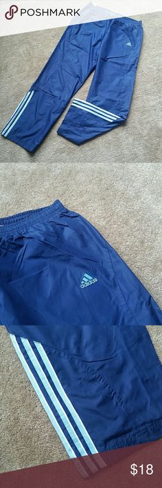 New Adidas women's navy blue wind pants New Adidas women's navy blue wind pants with white and light blue accents. Front has 2 pockets, 1 zip pocket in back, elastic waistband with draw string tie in front.  Material is wind suit material (100% polyster), inside light cotton like lining. Great pants, new never worn but no tags Adidas Pants Track Pants & Joggers
