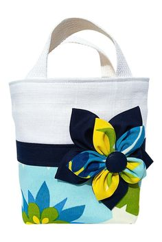Baby needs a beach bag, too! Outfit your little girl so she's ready to show off her mini-me style. This white linen, tropical print, and navy tote is exactly what she needs to complete her first or se