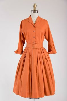 1950s vintage dress made of a burnt orange cotton. Fitted waist, shirtwaist bodice, elbow length cuffed sleeves and full pleated skirt. darting for fit. Pleat detail at back bodice. Buttons up the fro