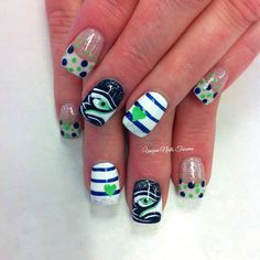 A super fun Seahawks nail design by Unique Nails Tacoma that features blue & white stripes, the blue & green dots over French Tips and of course a hand painted seahawk eye! #seahawks #nailart #manicure