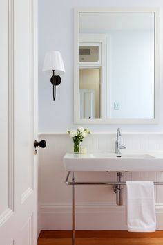 Beautiful guest bathroom with baby blue textured blue wallpaper paired with bathroom chair rail and beadboard.