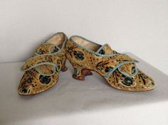 Pair of woman's hoes, 1770s. Velvet of taupe fine rib woven with blue centred flowers with black leaves, fruits and leaves in similar colours, edged with a grosgrain pale blue silk, lined in natural linen, the front with cross over latches, high tongue, slighty pointed toes, high shaped Louis heel, leather soldes, turnshoe construction.