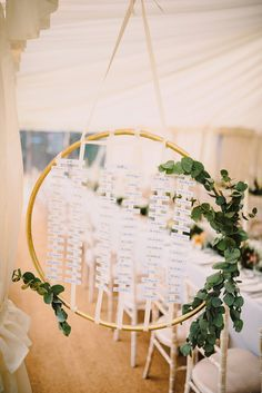 Hanging hoop wedding table plan decorated with foliage. Photography by Modern Vintage Weddings Photography