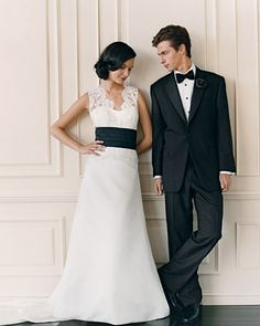 A custom-made black silk cummerbund is a modern touch to a delicate lace gown.