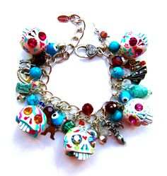 A Leandra Holder Day of The Dead sugar skulls charm bracelet - made in approx. 2010 - hand carved porcelain skulls with Swarovski crystals. This one has eclectic charms from various cultures - Mexican, Native American and Egyptian.