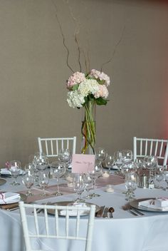 Tall wedding centerpiece of pink white hydrangea, gathered with curly willow branches into a tall glass cylinder vase