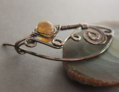 Shawl pin or scarf pin in swirly ornate design with rich honey color lampwork glass bead