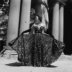 A terrifically glamorously 1952 Dorian Leigh gown modeled in front of classically stately architecture.