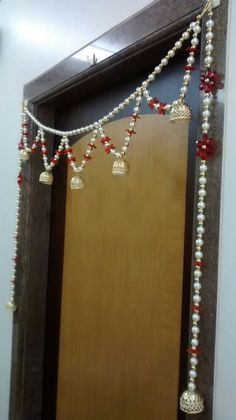 Pearl Toran with LED battery operated light - Strings of white pearls, gold beads and red acrylic flowers with LED light-embedded umbrella at bottom making it a perfect illuminated toran. Price : INR 1,500/- per piece. To inquire more or place an order, call or whatsapp us at +91 99 200 66 996