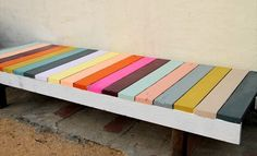 A colorful pallet bench with each top wood slat painted a different color.
