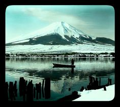MOUNT FUJI FROM THE DOCK PILINGS -- The Lone Boatman in Japan's Winter Light (Morning on Lake Yamanaka) | Ca.1898 Hand-tinted glass lantern-slide by T. Enami, Japan's Meiji-era Master of the small format image. Produced from one half of a stereoview negative.