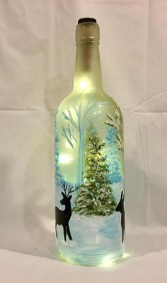 **Made to Order** Brighten your holiday decor with this gorgeous Christmas wine bottle light, hand painted with deer walking through a snowy forest. The word joy is written in the snow, but it can be customized with any word or phrase you would like. Painted with enamel paint and