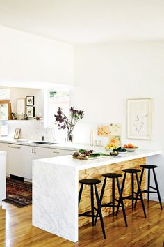 All white kitchen with a mix of white marble and wood, with breakfast bar and black bar stools.