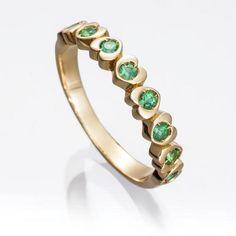 Alianza de esmeraldas CORAZONES Sortija tipo alianza en oro amarillo de 18 kts. montada con esmeraldas en talla redonda mixta.