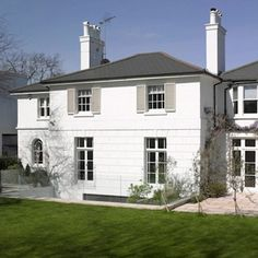 White stucco facade, window shutters, period house, slate roof