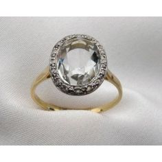 Circa 1920.  This beautiful Art Deco ring is centered by quartz crystal surrounded by sparkling diamonds.  The crystal has a very subtle green hue.  The metal is 18KT yellow gold.
