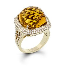 A remarkable 17.71 ct faceted citrine is the center focus of this 14k yellow gold Blindingly Beautiful ring which also contains .78 ctw of white diamonds.