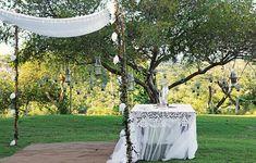 Várias lanternas foram penduradas na árvore sobre a mesa, que recebeu uma toalha branca de renda. Tudo para criar um altar com atmosfera romântica
